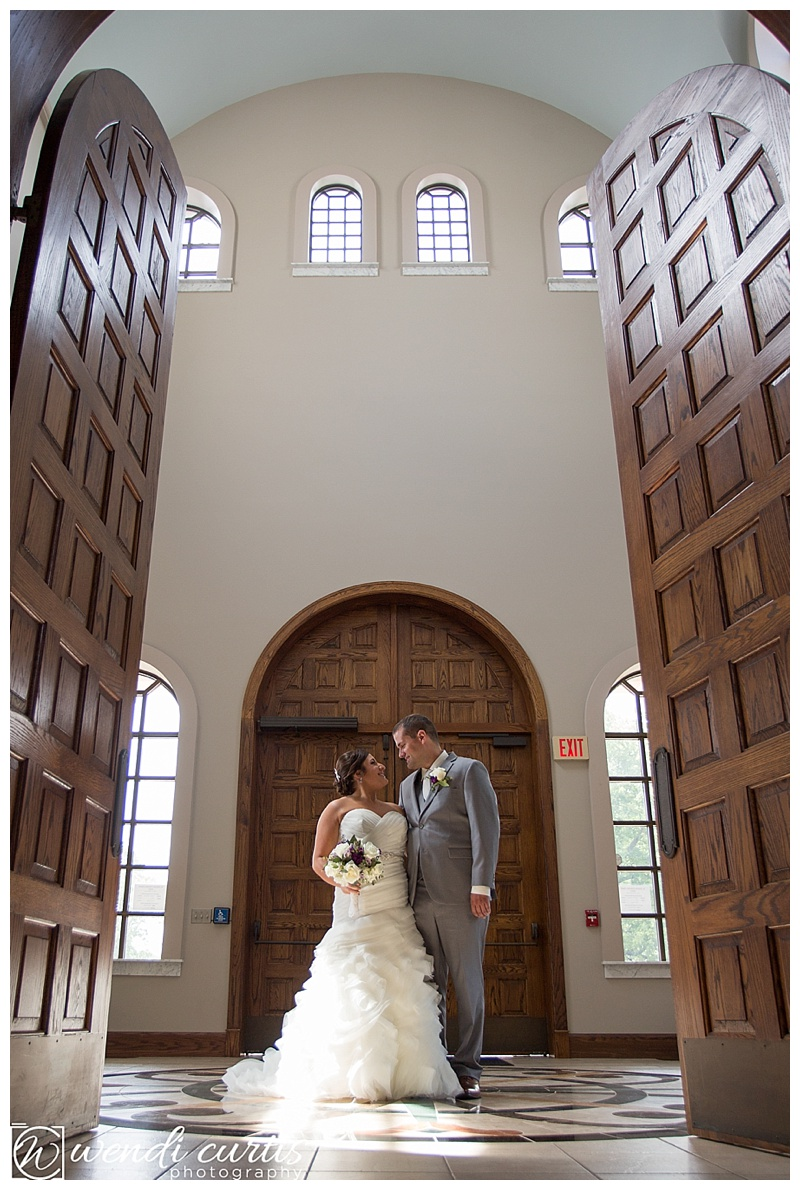 Bride and Groom inside Greek Orthodox church with large wooden doors